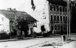 """widok na fragment ulicy Fromborskiej (Berlinerstrasse) ze zniszczeniami po wojnie. W miejscu istniejącego do dziś wyższego budynku dawniej stała karczma Hohekrug (Oberkrug), czyli Karczma Górna. W niższym budynku (dziś parking przy rondzie) po wojnie znalazła się restauracja """"Bagatelka""""."""