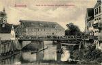 Most Młyński na przełomie XIX/XX wieku. W tej postaci przetrwał do 1914 r. zastąpiony wówczas znana obecnie betonowa konstrukcją.  W tle widoczny Młyn Miejski istniejący w tym miejscu od średniowiecza i to od niego najprawdopodobniej przyjęła się nazwa Most Młyński i Brama Młyńska.