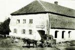 """Jeden z dyliżansów z dawnych czasów, który jeździł codziennie do I wojny światowej. Karczma w tle to zabytkowy budynek: jest to karczma """"Zum goldenen Kürbis"""" w Tharau (ob. Wladymirowo) na południe od Królewca, w której znajdował się przystanek dyliżansu. Właścicielem był Emil Ludwig. Takie dyliżanse przywoziły listy i paczki. Dla wielu ludzi było to bolesne pożegnanie, gdy wraz z rozwojem nowoczesnych środków transportu w całym kraju znikały pocztowe dyliżansy."""