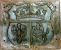 """Płyta herbowa żeliwna z kartuszem trójpolowym, przedstawiającym koronę jagiellońską, godło Rzeczypospolitej i Litwy. Taki herb był używany podczas powstania listopadowego 1830-1831. Ten konkretny eksponat Muzeum Ziemi Braniewskiej zainspirował autora do napisania tego artykułu. Tablica odnaleziona kilka lat temu na jednym z elbląskich złomowisk, uratowana dotarła do Gronowa skąd pozyskał ją przyjaciel autora. Rok czasu zajęło mi przekonanie ostatniego właściciela, aby tablica trafiła do muzeum. Stąd też zainteresowanie się """"polskimi"""" fragmentami historii Braniewa pod zaborem pruskim."""