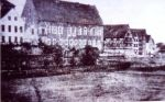 """Najstarsze istniejące zdjęcie dawnego zamku biskupiego z 1874 r. Niedługo później został zburzony i zastąpiony budynkiem w stylu neogotyckim. W dniu 11.09.1896r. w centrum miasta właśnie w pobliżu Szkoły Zamkowej spłonęło 13 budynków, w tym widocznych z prawej strony 7 spichrzy. Budynków tych już nie odbudowano, a w ich miejsce powstały kamienice. Obecnie z zamku pozostała Wieża Bramna, a w miejscu spichrzy straszy dziura w ziemi pod """"przyszłą"""" zabudowę."""