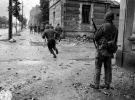 amerykańscy żołnierze przebiegają pod ostrzałem niemieckich snajperów ulicę w Cherbourgu